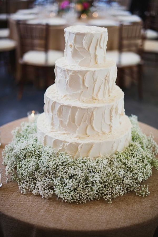 white-four-layer-wedding-cake-with-babys-breath-flowers-at-base